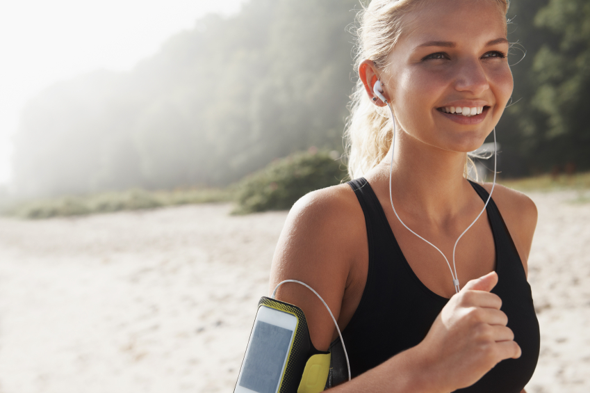 Attractive female jogger on the beach while out for a jog with a smile